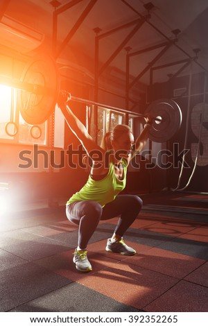 Muscular fitness woman deadlift a barbell over his head crossfit in the gym. Sports, crossfit and fitness - concept of healthy lifestyle. Woman in the fitness club. Crossfit woman. Crossfit style - stock photo