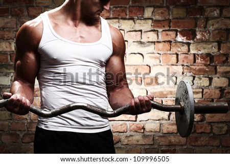 Muscular guy doing exercises with barbell against a brick wall