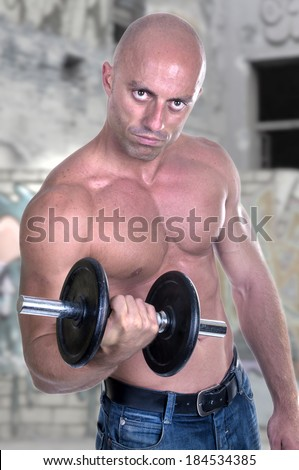 Muscular guy doing exercises with dumbbell outdoor - stock photo
