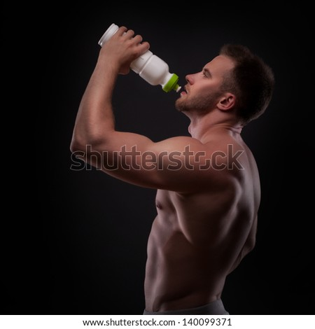 Muscular guy drinking water after training isolated on white background - stock photo