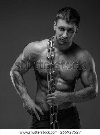 Muscular guy holds chain. Black and white photo - stock photo