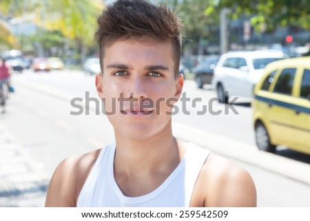 Muscular guy in the city looking at camera