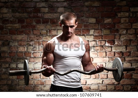 Muscular guy is training  biceps with barbell against a brick wall - stock photo