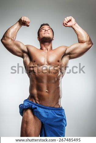 Muscular guy posing in studio on grey background. - stock photo