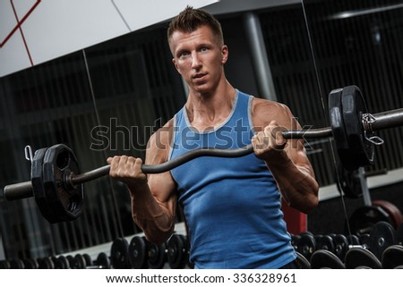 Muscular guy training his arms in gym