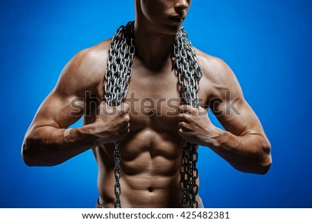 Muscular guy with chains on his shoulders against a blue background - stock photo