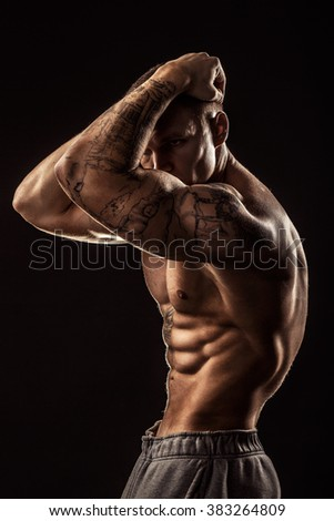 Muscular guy with tattoo holding his head. Isolated on dark background - stock photo