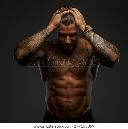 Muscular guy with tattooes holding his head. Isolated on grey background