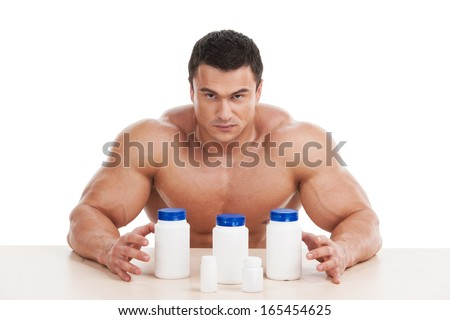 Muscular handsome bodybuilder with pills and dope. Sitting isolated over white background