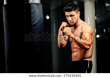 muscular handsome man fighter with boxing bag in gym - stock photo