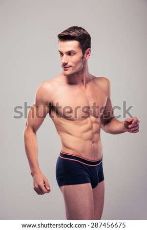 Muscular handsome man looking away over gray background - stock photo