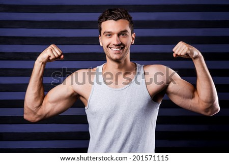 Muscular handsome. Muscular young man in tank top showing his perfect biceps and smiling while standing against striped background - stock photo