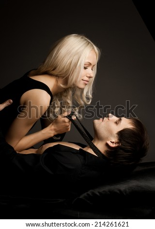 muscular handsome sexy guy with pretty woman, on dark background - stock photo