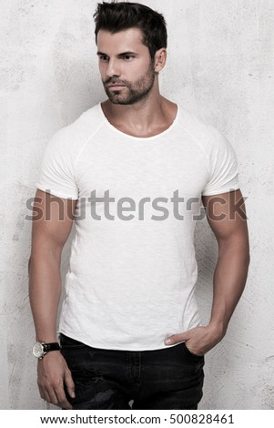 Muscular handsome young man posing in studio. Fashionable clothes.