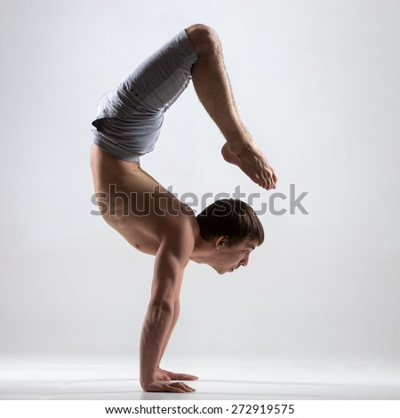 Muscular handsome young man working out, yoga, pilates, fitness training, doing handstand, asana Vrischikasana 2, Scorpion Pose, profile view, low key shot - stock photo