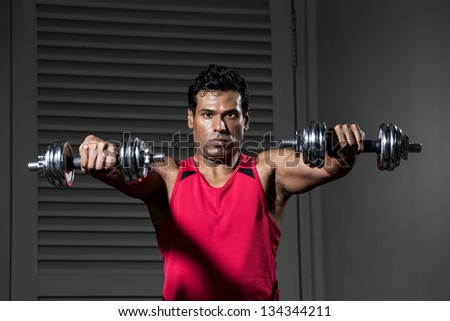 Muscular Indian man exercising with weight training equipment at a sports gym. - stock photo