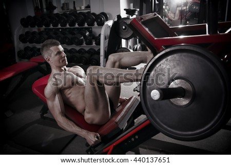Muscular legs. Handsome bodybuilder workout on trainer in the gym. Perfect male body