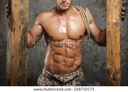 Muscular male body between two boards with rope on shoulder - stock photo