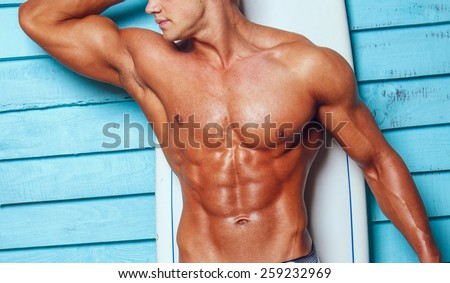 Muscular male body on blue background. - stock photo