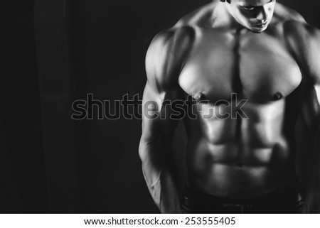 Muscular male bodybuilder, on a dark background. black and white photo - stock photo