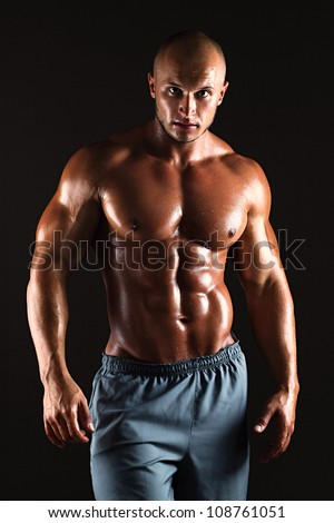 Muscular male bodybuilder on black background - stock photo