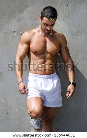 Muscular male bodybuilder standing against wall outdoors shirtless, wearing white boxer shorts