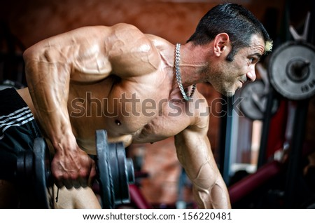 Muscular male bodybuilder working out in gym, exercising triceps leaning on a bench - stock photo