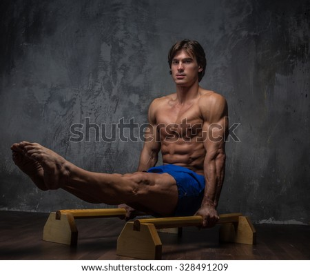 Muscular male doing gymnastic exercises on a floor. - stock photo