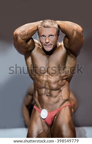 Muscular male flexing abs. Bodybuilder with abs posing. Aesthetic proportions of young athlete. Man dedicated to sport. - stock photo