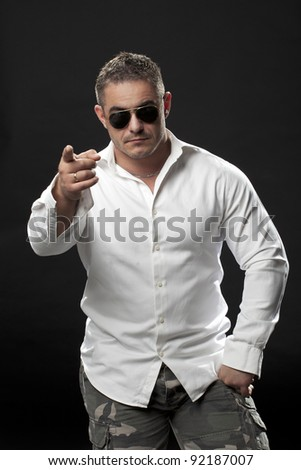Muscular male in a white shirt and sunglasses standing and pointing with his finger
