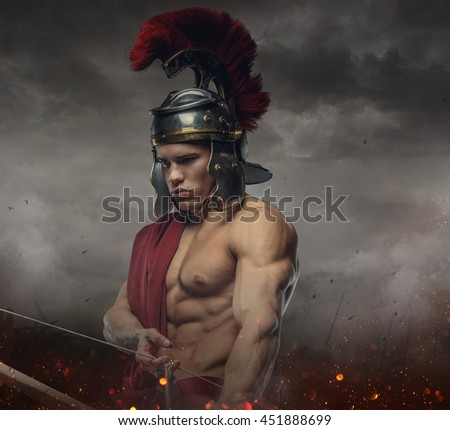 Muscular male in spartan costume holding wooden bow under stormy sky. - stock photo