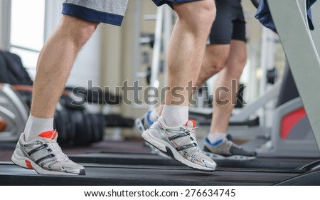 Muscular male legs on a treadmill at the gym - stock photo