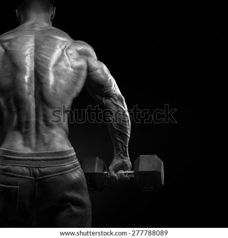 Muscular male model bodybuilder doing exercises with dumbbells, turned back. Isolated over black background. Black and white photo. - stock photo