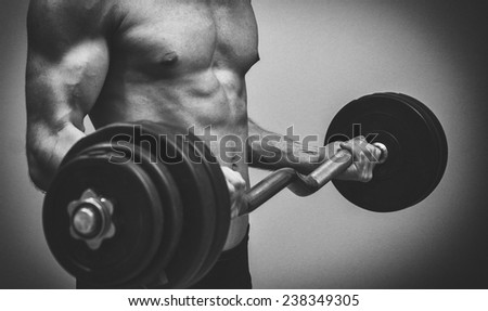 Muscular male model doing exercises with barbell. Black and white.