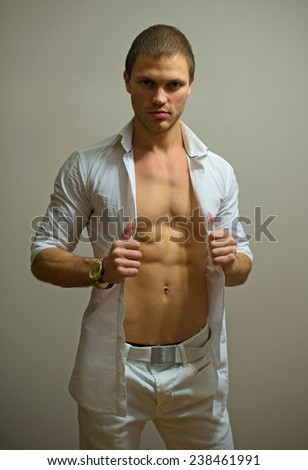 Muscular male model posing on grey background.