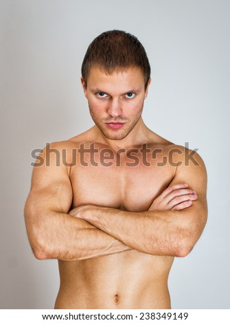 Muscular male model with arms folded.