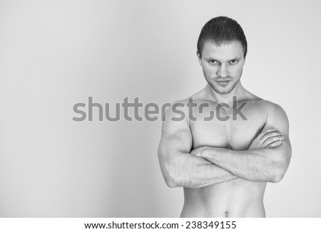 Muscular male model with arms folded. Black and white. Place for text.