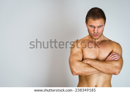 Muscular male model with arms folded. Place for text. - stock photo