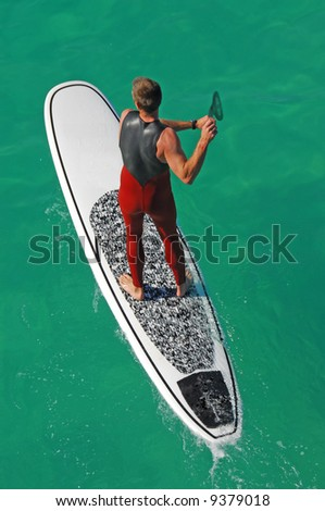 Muscular male on surfboard with paddle - stock photo