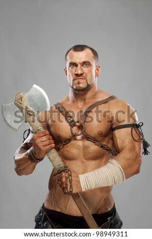 muscular male portrait of ancient warrior with axe - stock photo