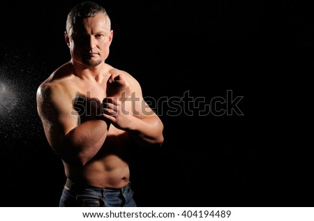 Muscular male posing on black background - stock photo