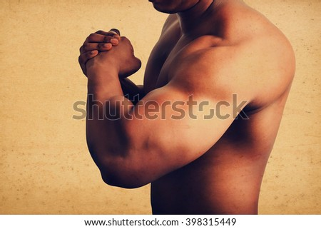 Muscular male showing big arm muscles, grunge vintage style. - stock photo
