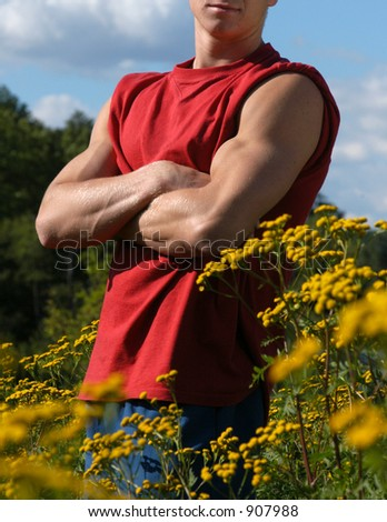 Muscular male torso on a meadow - stock photo
