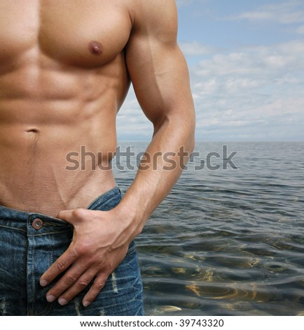 Muscular male torso on the beach - stock photo