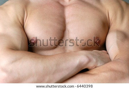 Muscular male torso with crossed hands - stock photo