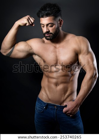 muscular male torso with six pack of a fit bodybuilder in jeans on black background - stock photo