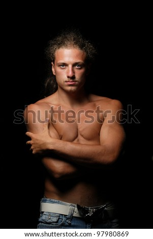 Muscular male with long air on black background. - stock photo