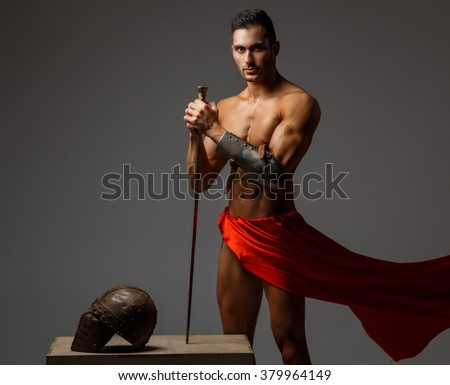 Muscular man ancient Rome soldier holding a sword dressed in a red fluttering dress. - stock photo
