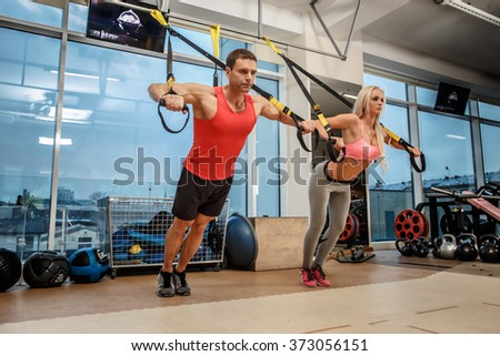 Muscular man and athletic woman doing exercises with expander in a gym. - stock photo