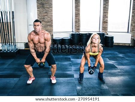 Muscular man and fit woman doing exercises with kettle ball at gym - stock photo